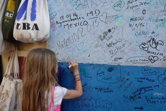 Daughter Rubi writers her name on the wall at La Bodequita del Medio.